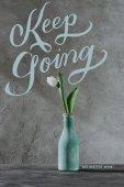 Fotografie weiße Feder Tulpen in blauer Vase und Keep Going Schriftzug auf graue Oberfläche