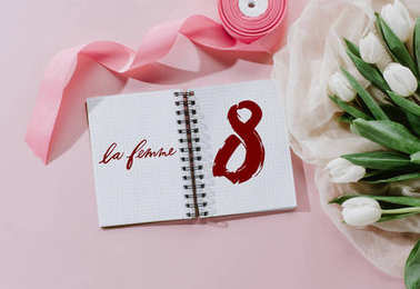 top view of LE FEMME sign in notepad, pink ribbon and white tulips for international women day