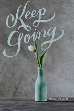 white spring tulip in blue vase and KEEP GOING lettering on grey surface