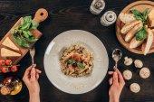 abgeschnittenes Bild einer Frau, die Gabel und Löffel in der Hand hält und Pasta essen geht