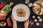 abgeschnittenes Bild einer Frau, die einen Teller mit Nudeln auf den Tisch stellt