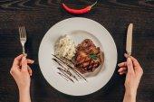 Fotografie oříznutý obraz ženy držící vidličku a nůž poblíž deska s hovězí steak