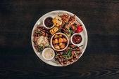 Fotografie pohled shora desky s hovězí steaky, kuřecí křidélka a grilovanou zeleninou na dřevěný stůl