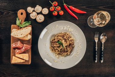 top view of pasta on plate and meat on wooden board
