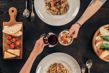 cropped image of lesbian couple clinking with glasses of wine at restaurant