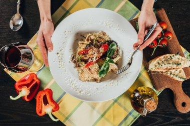 cropped image of woman eating vegetarian pasta