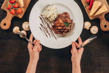 cropped image of woman holding plate with beef steak