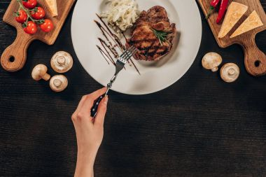 cropped image of woman holding fork and going to eat beef steak