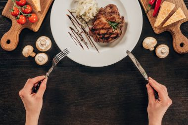 cropped image of woman holding fork and knife above plate with beef steak