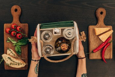 cropped image of woman holding wooden box with olive oil and pepper grinder
