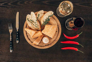 top view of parmesan cheese with baguette slices on wooden board, chili peppers and wine on table