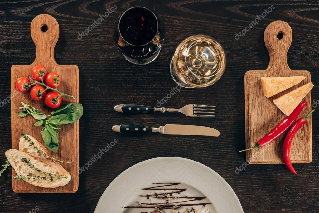 top view of glasses of wine and parmesan cheese with vegetables on tabletop