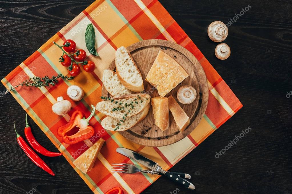 top view of bread and parmesan cheese on wooden board