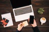 abgeschnittenes Bild der Geschäftsfrau Hände halten Smartphone und Bleistift, Laptop