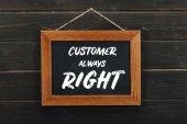 Deska s nápisem zákazníka vždy pravdu zavěšené na dřevěné stěně obrazce