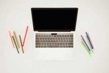 Laptop with blank screen between colorful felt pens on white surface