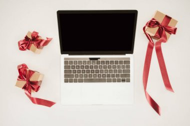 Laptop with blank screen between gift boxes on white surface