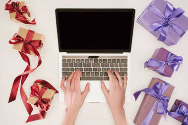 Top view of businesswoman hands on laptop between gift boxes