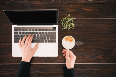 Cropped view of woman hands on laptop with blank screen and coffee cup