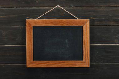 Empty blackboard hanging on wooden wall
