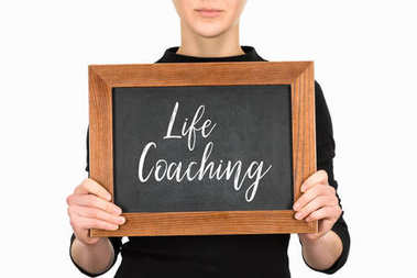 Cropped view of woman holding board with lettering life couching isolated on white