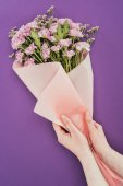 cropped shot of person holding beautiful floral bouquet wrapped in pink craft paper on violet