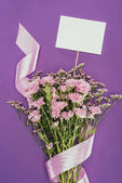 Photo bouquet of beautiful pink flowers with ribbon and blank card on violet