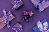 Fényképek ajándék dobozok, lila szalag és gyönyörű virágok a lila felső nézetében