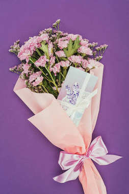 beautiful floral bouquet with pink ribbon and greeting card on violet