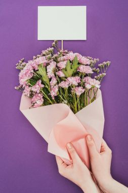 cropped shot of person holding beautiful floral bouquet with blank card on violet