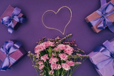 bouquet of beautiful pink flowers, heart-shaped rope and gift boxes on violet