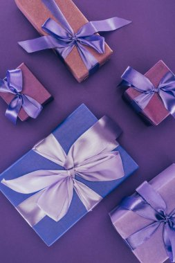 top view of decorative gift boxes with ribbons and bows on purple