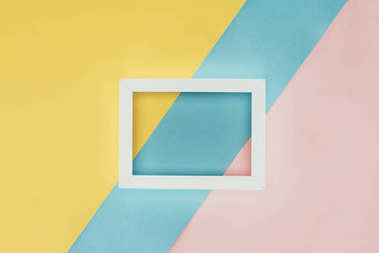 top view of white empty wooden frame on colorful background