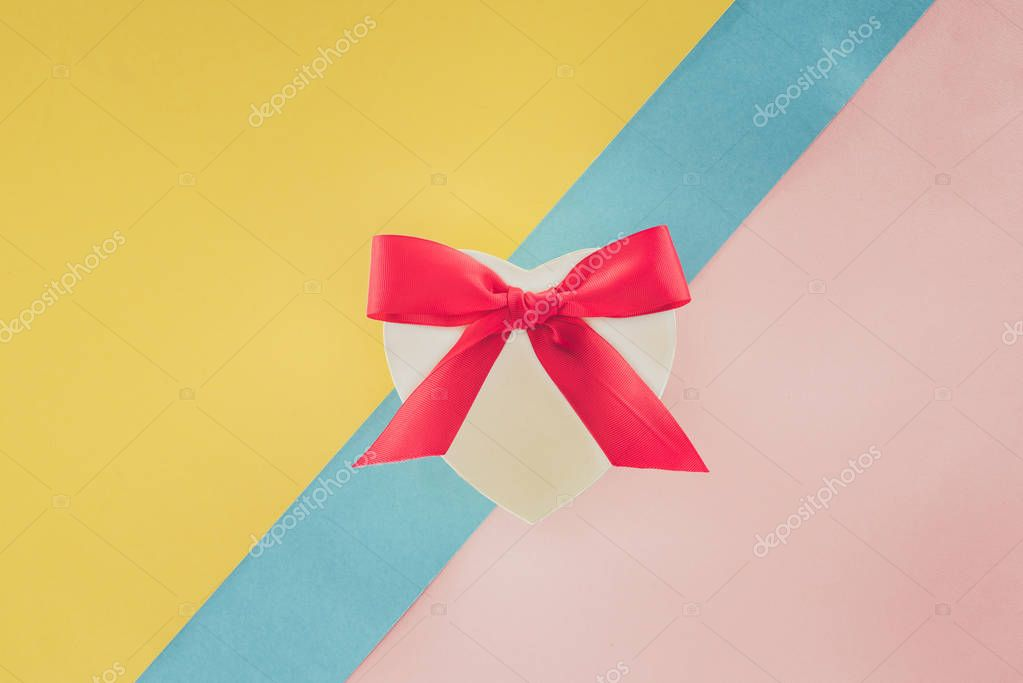 Top view of white heart shaped gift with pink ribbon on colorful background