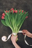 Oříznout záběr osoby dekorační kytice z krásné tulipány s mašlí