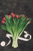 krásná kytice z červený tulipán a stuha na tmavý podklad