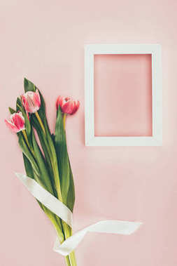 bouquet of beautiful pink tulips with ribbon and empty white frame on pink