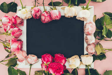 top view of frame made from beautiful pink roses and blank white frame on pink