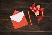 pohled shora červené obálky s prázdný papír a dárkové krabice na dřevěný stůl