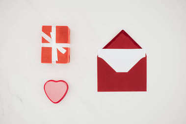 top view of red envelope with blank paper and gift boxes isolated on white