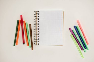 top view of blank notebook with colorful markers isolated on white