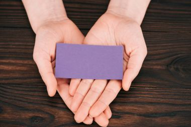 cropped shot of woman holding blank purple paper over wooden table