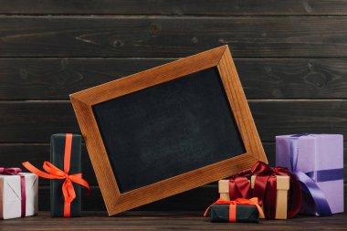 blank chalkboard in frame with various gift boxes against wooden wall
