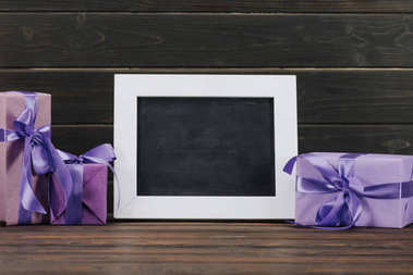 blank blackboard in frame with gift boxes against wooden wall