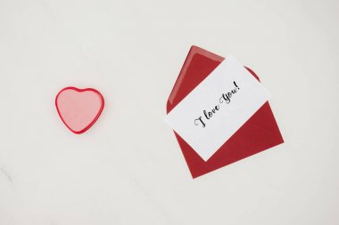 top view of red envelope with i love you lettering on paper and heart shaped box isolated on white
