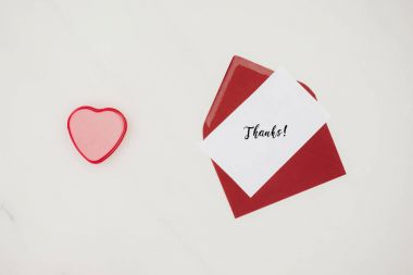 top view of red envelope with THANKS lettering on paper and heart shaped box isolated on white