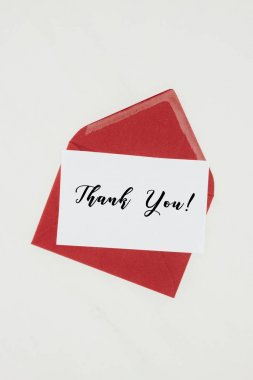 top view of red envelope with THANK YOU lettering on paper isolated on white