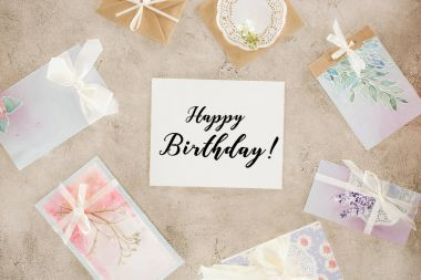 top view of paper with happy birthday lettering surrounded with greeting cards on concrete surface