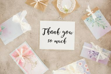top view of paper with thank you lettering surrounded with greeting cards on concrete surface