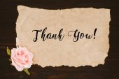 Photo top view of aged paper with thank you lettering and rose flower on wooden table